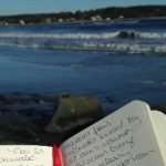 View of an ocean beach with a journal with writing in it in the foreground