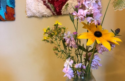 flowers in vase with hooked mats on the background