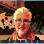 Screen shot of Meryl on Zoom with her hooked rugs in the background.