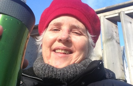 Woman with white hair, red beret, holding a thermal mug of tea, wearing a parka and wool sweater. Winter tea on the deck.