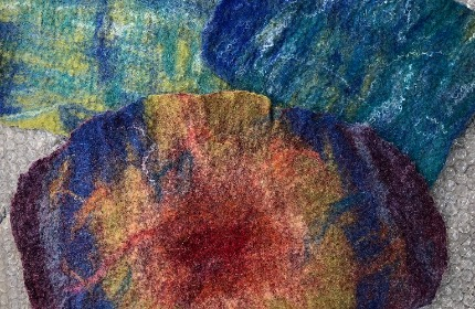 Three pieces of fabric that have been wetfelted. Two are green/blues and the third is the Chakra colours in a circle, starting with red, then orange, yellow, green, blue and violet