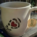 White mug with a heart and sole design on a wooden deck table. Stash t-bag on the handle of the mug. Blue pen to the side.